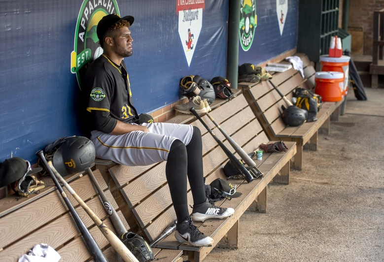 FILE – In this Sept. 1, 2019, file photo, Bristol Pirate's starting pitcher Adrian Florencio sits alone in the dugout while his teammates are at bat during a baseball game in Johnson City, Tenn. Some towns who have found their minor league teams on a possible Major League Baseball list of 42 teams to eliminate have begun fighting back. (David Crigger/Bristol Herald Courier via AP, File)
