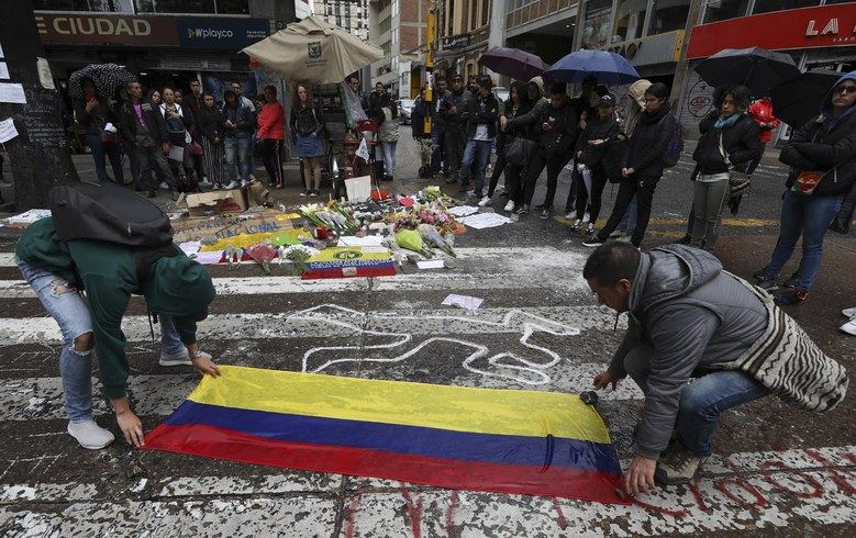 Students place a Colombian national flag at the site where Dilan Cruz was injured during clashes between anti-government protesters and security forces in Bogota, Colombia, Tuesday, Nov. 26, 2019. Cruz, an 18-year-old high school student, died two days after being hit in the head by a projectile reportedly fired by riot police during a protest. His case has resonated in Colombian society, touching off a debate about excessive use of force and making him a symbol for many young protesters. (AP Photo/Fernando Vergara)