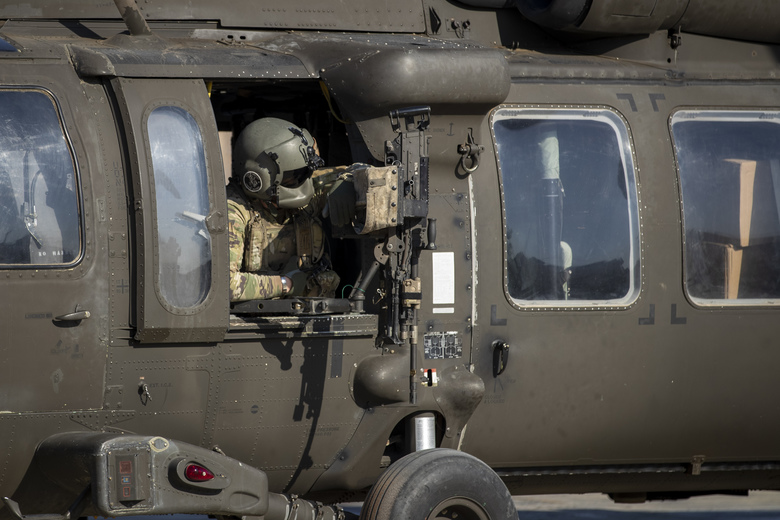 A helicopter gunner waits for takeoff at a US military base at an undisclosed location in Eastern Syria, Monday, Nov. 11, 2019. The deployment of the mechanized force comes after US troops withdrew from northeastern Syria, making way for a Turkish offensive that began last month. (AP Photo/Darko Bandic)