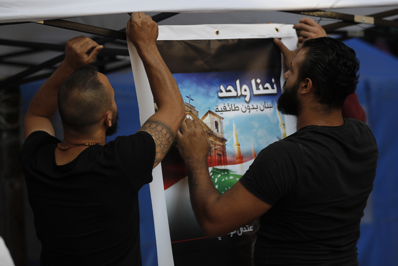 "In this Thursday, Nov. 7, 2019, Shiite anti-government protesters install an Arabic placard that reads, "" We are one, Lebanon without sectarianism,"" in downtown Beirut, Lebanon. Lebanon's protests have brought out people from across the country's spectrum of faiths and communities trying to throw out the entire ruling elite. They give a glimpse into a Lebanon transcending longtime divisions among Muslims, Christians and other sects. (AP Photo/Hussein Malla)"