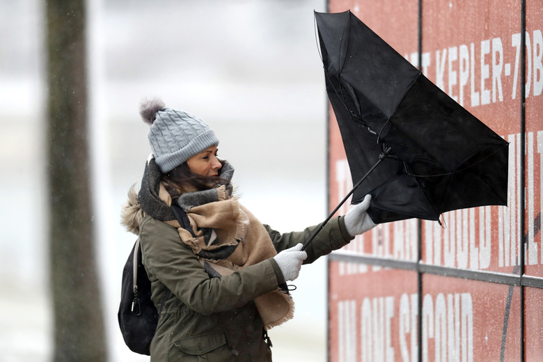 A woman walking the half mile from the Chicago Aquarium to the Adler Planetarium fights a stiff wind inverting her umbrella in the blowing snow off Lake Michigan, Monday, Nov. 11, 2019, in Chicago. (AP Photo/Charles Rex Arbogast)