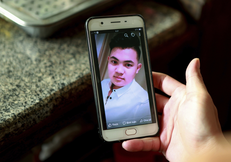 FILE – In this Oct. 28, 2019 file photo, Hoang Thi Ai, mother of Hoang Van Tiep, who is feared to be among the England truck dead, hold a phone showing a photo of Tiep in Dien Thinh village, Nghe An province, Vietnam. Ten teenagers were among the 39 Vietnamese found dead in a truck container in southeast England last month, local police said Friday, Nov. 8 while relaying for the first time details of those who died. Two of the dead were only 15, while the oldest was 44. Some 20 of the victims came from one province — Nghe An in north central Vietnam, around 200 kilometers (120 miles) south of Hanoi. Hoang Van Tiep was among the dead. (AP Photo/Hau Dinh)