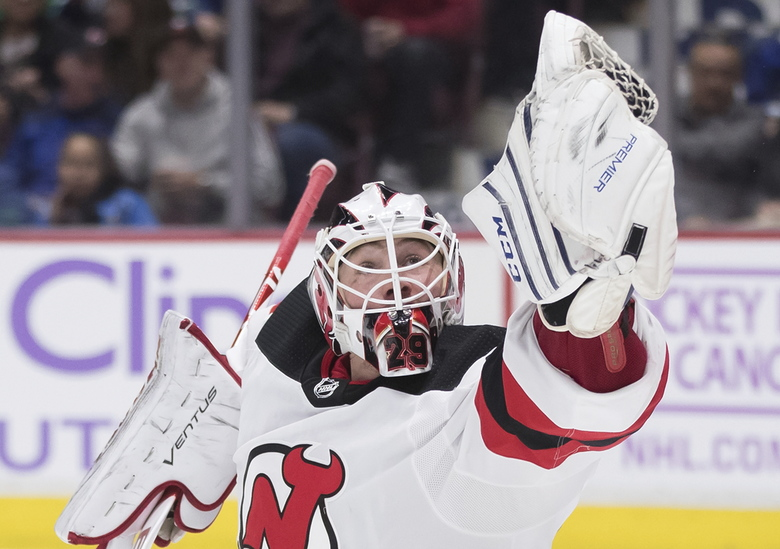 New Jersey Devils goalie MacKenzie Blackwood makes a glove-save during the second period of an NHL hockey game against the Vancouver Canucks in Vancouver, British Columbia, Sunday, Nov. 10, 2019. (Darryl Dyck/The Canadian Press via AP)