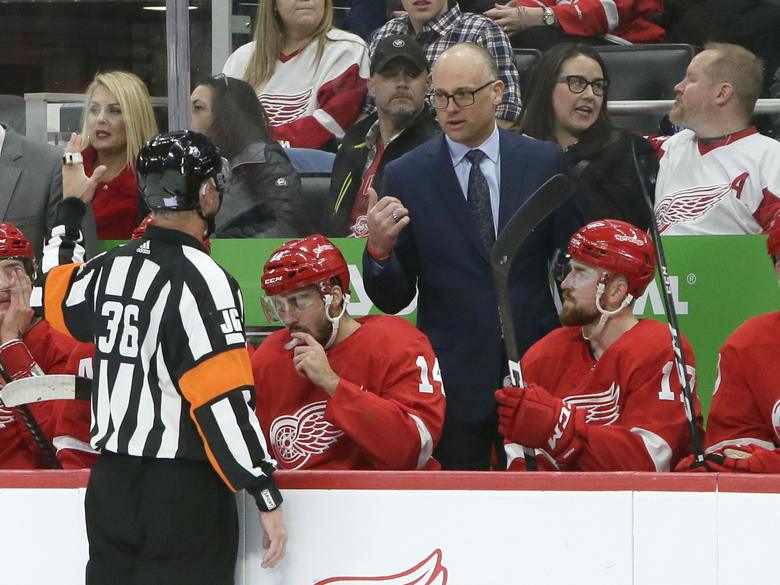 Detroit Red Wings head coach Jeff Blashill, center top, talks with referee Dean Morton (36) during the first half of an NHL hockey game against the Carolina Hurricanes, Sunday, Nov. 24, 2019, in Detroit. (AP Photo/Duane Burleson)