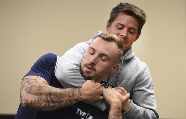Ryan Russo, left, and Mike Herrall go through a drill during a defensive tactic training class at the American Medical Response training center in Clackamas, Ore., on Sept. 10. (Steve Dykes / AP)
