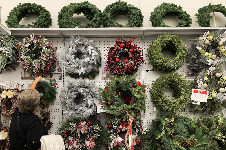FILE – In this Nov. 9, 2019, file photo a woman looks through holiday wreathes on sale at a retail store during in Pembroke Pines, Fla. On Tuesday, Nov. 26, the Conference Board reports on U.S. consumer confidence for November. (AP Photo/Brynn Anderson, File)