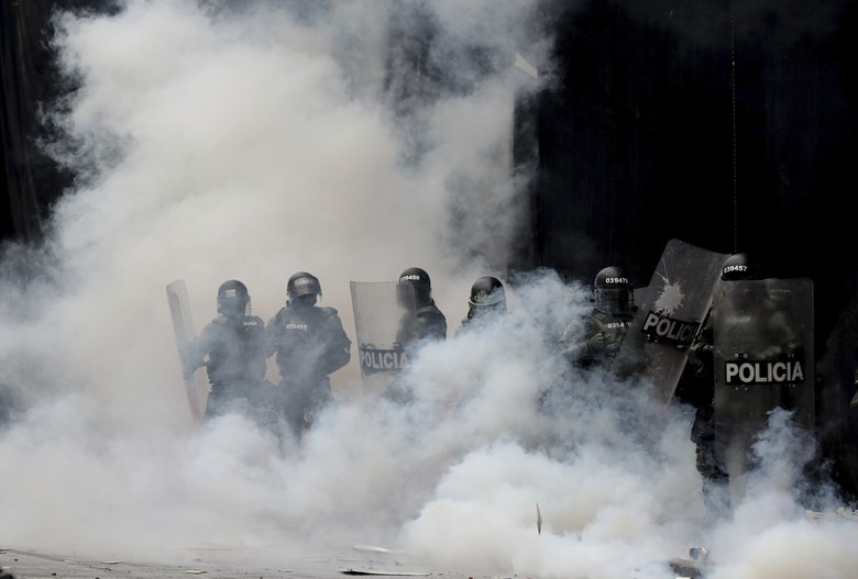 Police are engulfed by a cloud of tear gas after dispersing anti-government protesters at Bolivar square in downtown Bogota, Colombia, Thursday, Nov. 21, 2019. Colombia's main union groups and student activists called for a strike to protest the economic policies of Colombian President Ivan Duque government and a long list of grievances. (AP Photo/Fernando Vergara)