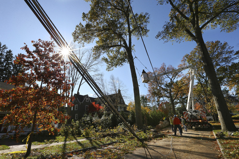 Crews from Madison Electric and Butler Municipal Power and Light work on downed power lines on Green Hill Road Friday, Nov. 1, 2019, in Madison, N.J. The borough was hit by high winds on heavy rain late the night before. (AP Photo/Rich Schultz)
