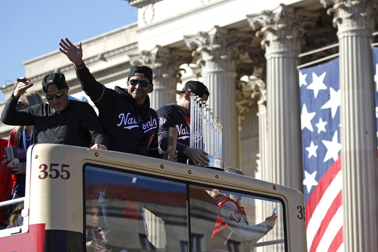 Washington Nationals manager Dave Martinez (4) waves to fans during a parade to celebrate the team's World Series baseball championship over the Houston Astros, Saturday, Nov. 2, 2019, in Washington. (AP Photo/Patrick Semansky)