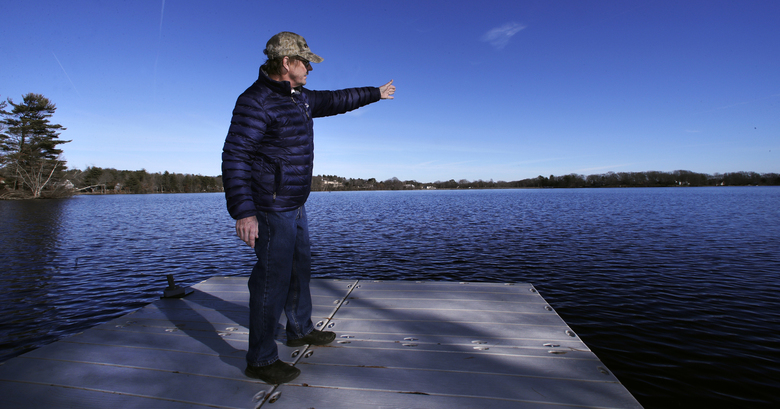 """In this Dec. 27, 2018, photo, Murray Beach, an investment banker who lives on the shore of Willett Pond, points out the spillway of the lake, which is located on the border of Norwood and Walpole, Mass. The spillway at the 107-year-old Willett Pond Dam is capable of handling just 13% of the water flow from a serious flood before the dam is overtopped, according to a recent state inspection report. """"We are not talking of just flooding someone's house. We are talking about covering their house,"""" said Beach, who belongs to a citizens group that has lobbied for years for the spillway to be repaired. (AP Photo/Charles Krupa)"""