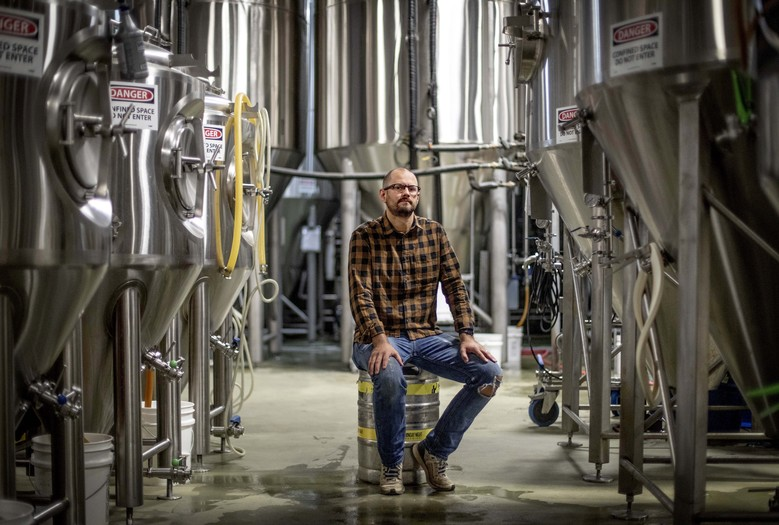 """Joel Iverson, chief operating officer of Monday Night Brewing, is photographed in the brewery that sits beside Reservoir No. 1, a 180 million-gallon water supply that has been out of service much of the past few decades, Oct. 15, 2019, in Atlanta. Iverson has previously noticed water trickling out of the hillside of the dam near the brewery he co-founded. """"If that one goes, it's going to wash away us and a lot of beer,"""" said Iverson. (AP Photo/David Goldman)"""