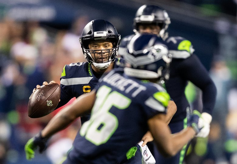 Russell Wilson eyes wide receiver Tyler Lockett on Sunday. (Andy Bao / The Seattle Times)