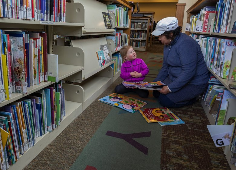 Millicent Dann, 3, reads a book with her nanny Estela Tapia during their visit at the Columbia branch of the Seattle Public Library. Millicent lives close by and the two often walk to the library to read. Her mother says that Millicent is a total bookworm. (Ellen M. Banner / The Seattle Times)