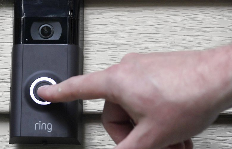 FILE – In this Tuesday, July 16, 2019, file photo,  pushes the doorbell on his Ring doorbell camera. Amazon-owned doorbell camera company Ring is neighborhoods.(AP Photo/Jessica Hill, File) NY112