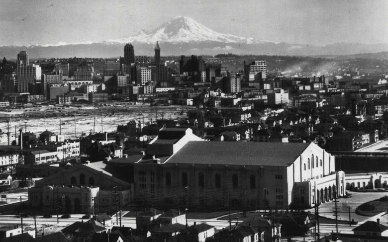 Civic Auditorium (center) and Civic Ice Arena (left) opened in 1928 at  Seattle's Civic Center, on what is now known as Seattle Center. The buildings are photographed here in 1930, from Queen Anne Hill. Civic Field is to the right of the auditorium. (UW Libraries, Special Collection)