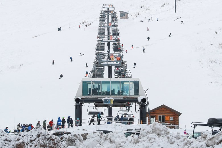 Skiers and snowboarders at The Summit wait to ride the lift up one of the lines at The Summit at Snoqualmie on Christmas Day.  (Andy Bao / The Seattle Times)