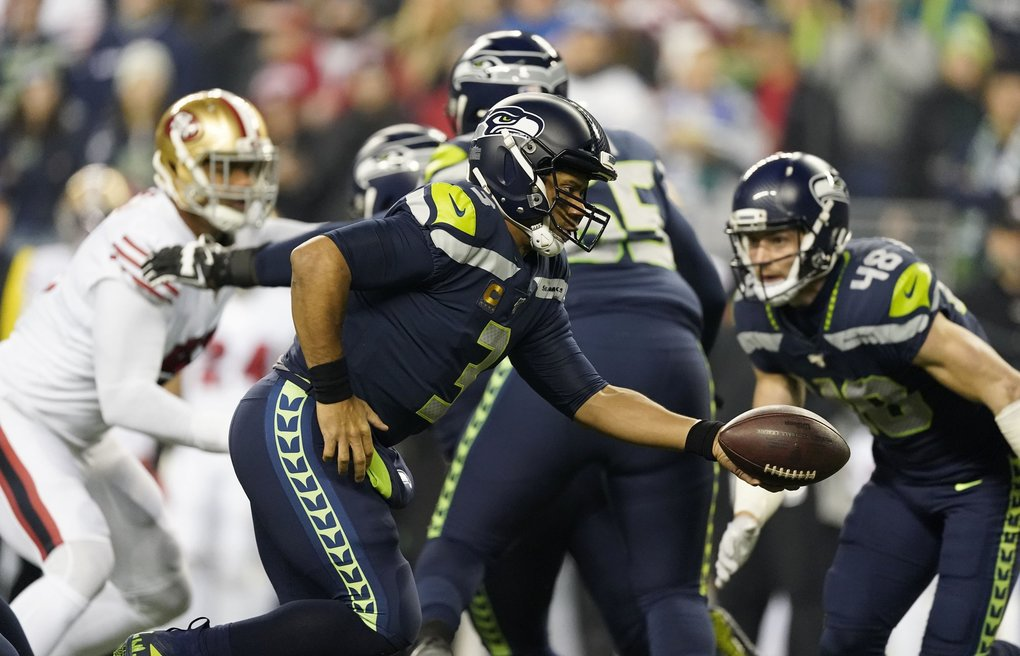 Seattle Seahawks quarterback Russell Wilson looks to hand off under pressure from the 49ers defense during the opening drive in the first quarter, which ended with a punt, as the Seahawks play the San Francisco 49ers Sunday, December 29, 2019 at CenturyLink Field in Seattle.  (Dean Rutz / The Seattle Times)