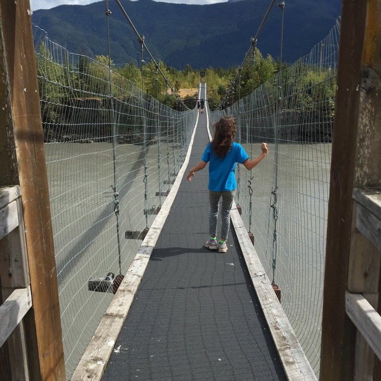 "The operative word for many families with kids with disabilities is ""outdoors"" when it comes to travel. Olivia Duin is shown here crossing a bridge over the Nass River near Gitwinksihlkw, in Nisga'a territory in British Columbia. (Julia Duin)"
