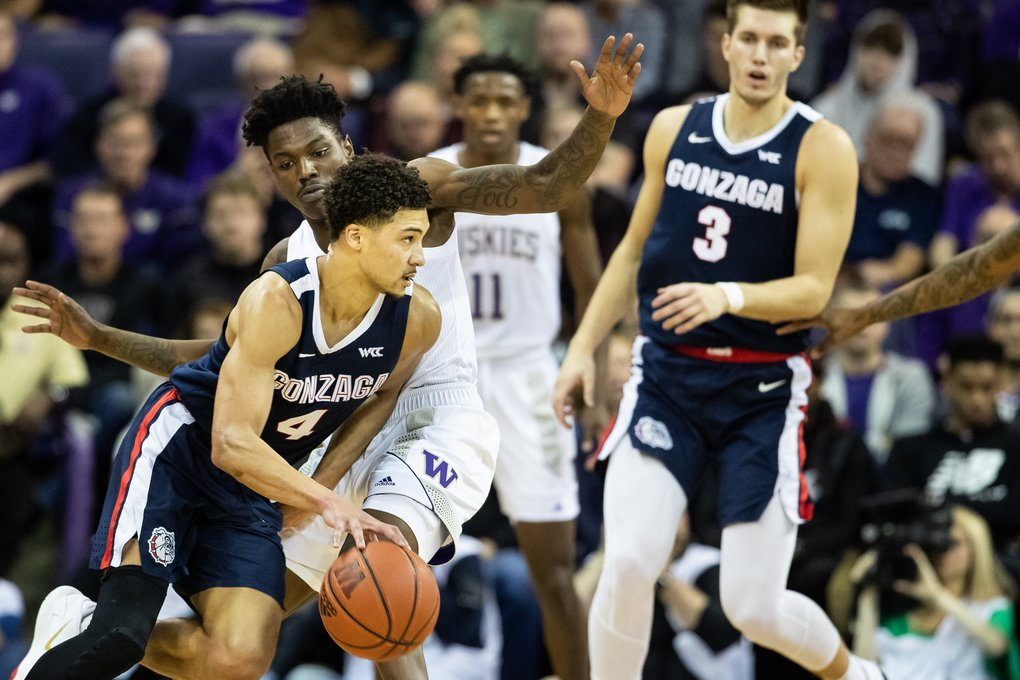 Gonzaga Bulldogs guard Ryan Woolridge (4) maneuvers around Washington Huskies guard Elijah Hardy (10) during the first half of the NCAA men's basketball game between University of Washington and Gonzaga University at Alaska Airlines Arena on Dec. 8, 2019. (Andy Bao / The Seattle Times)