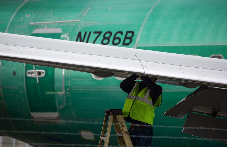 An employee works on the wing of a 737 MAX in Renton. (David Ryder/Bloomberg)