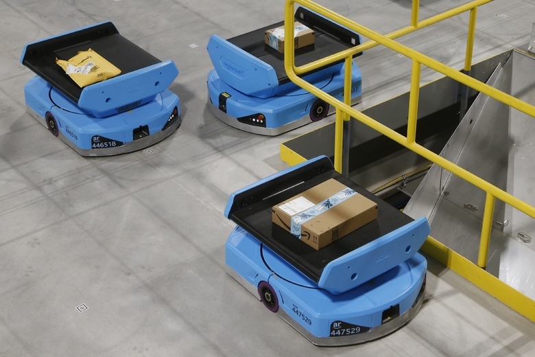 """Amazon robots move along the warehouse floor with packages before finding the proper delivery chute, transporting packages from workers to chutes that are organized by zip code, at an Amazon warehouse facility in Goodyear, Ariz, in December. Amazon and its rivals are increasingly requiring warehouse employees to get used to working with robots. The company now has more than 200,000 robotic vehicles it calls """"drives"""" that are moving goods through its delivery-fulfillment centers around the U.S. (AP Photo / Ross D. Franklin)"""