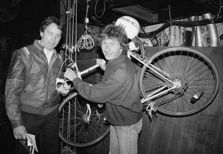 """FILE – In this May 16, 1985, file photo, actor John Ritter, left, checks out the bicycle of fellow actor Rene Auberjonois, center, backstage at the Eugene O'Neill Theatre in New York following a performance of the Broadway musical, """"Big River: The Adventures of Huckleberry Finn."""" Auberjonois, a prolific actor best known for his roles on the television shows """"Benson"""" and """"Star Trek: Deep Space Nine"""" and his part in the 1970 film """"M.A.S.H."""" playing Father Mulcahy, died Sunday, Dec. 8, 2019. He was 79. (AP Photo/Ron Frehm, File)"""