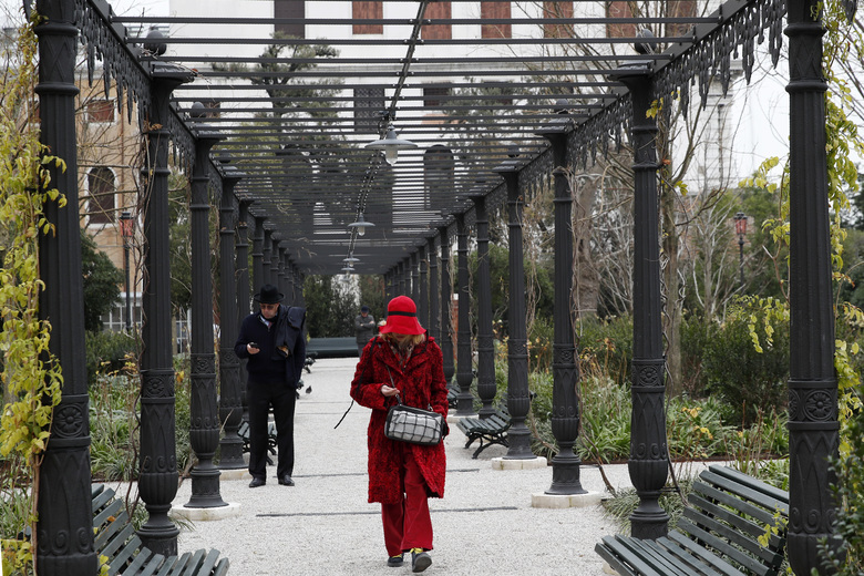 People visit the newly restored Royal Gardens in Venice, Italy, Tuesday, Dec. 17, 2019. Venice's Royal Gardens were first envisioned by Napolean, flourished under Austrian Empress Sisi and were finally opened to the public by the Court of Savoy, until falling into disrepair in recent years. After an extensive restoration, the gardens reopened Tuesday as a symbol both of the lagoon city's endurance and the necessity of public-private partnerships to care for Italy's extensive cultural heritage. (AP Photo/Antonio Calanni)
