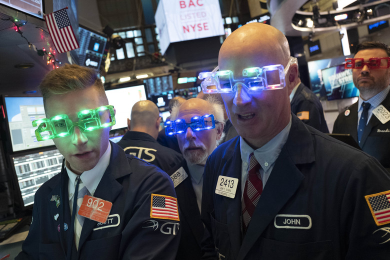 Stock traders wear New Year's 2020 party glasses at New York Stock Exchange on Tuesday. Wall Street closed the books Tuesday on a blockbuster 2019 for stock investors, with the broader market delivering its best returns in six years. (AP Photo/Mark Lennihan)