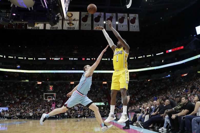 Los Angeles Lakers guard Kentavious Caldwell-Pope (1) attempts a three-point basket as Miami Heat forward Kelly Olynyk defends during the first half of an NBA basketball game, Friday, Dec. 13, 2019, in Miami. (AP Photo/Lynne Sladky)