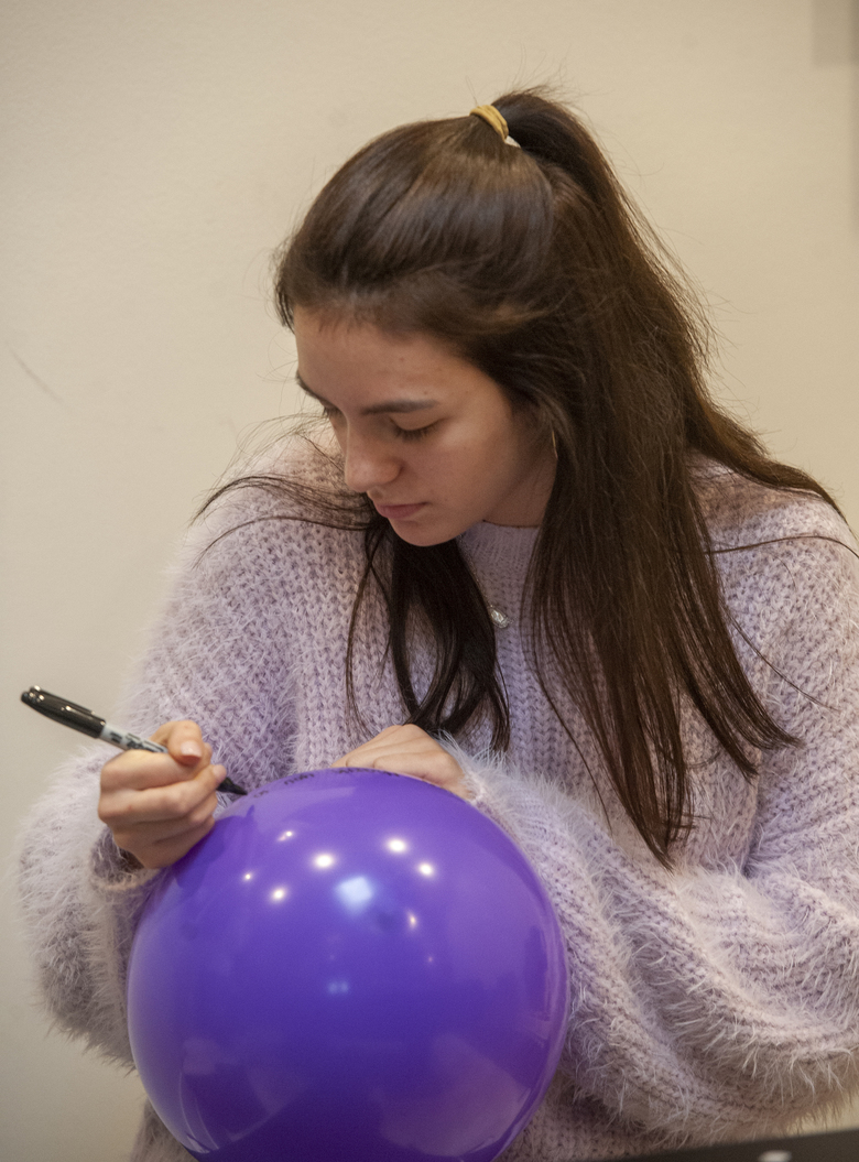 Friend and classmate of Walker Vincent Grace Morgan write a note to him on a balloon during a16th birthday party for him at Leslie Jacob's home on Sunday, December 29, 2019 in Lafayette, La. Walker Vincent was one of the victims in the plane crash on Saturday. Family and friends threw him a birthday party where they released LSU balloons and marked gifts with their favorite memories of Walker for his father.  (Brad Kemp/The Advocate via AP)
