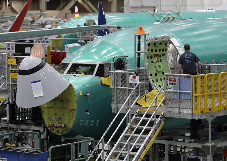 FILE – In this March 27, 2019, file photo, a worker enters a Boeing 737 MAX 8 airplane during a brief media tour of Boeing's 737 assembly facility in Renton, Wash. On Monday, Dec. 16, shares of Boeing are falling before the opening bell on a report that the company may cut production of its troubled 737 Max or even end production all together. (AP Photo/Ted S. Warren, File)