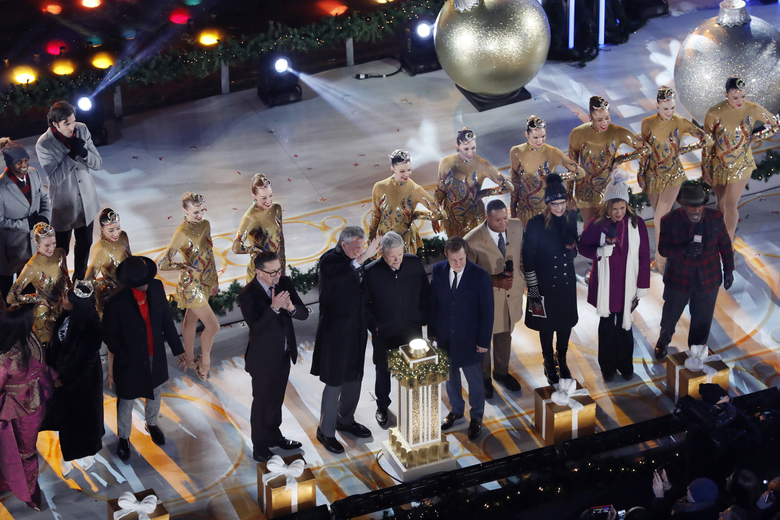 New York Mayor Bill de Blasio, in dark coat, second from left foreground, waves as he prepares to push the button to illuminate the 87th annual Rockefeller Center Christmas Tree lights, Wednesday, Dec. 4, 2019, in New York. (AP Photo/Kathy Willens)