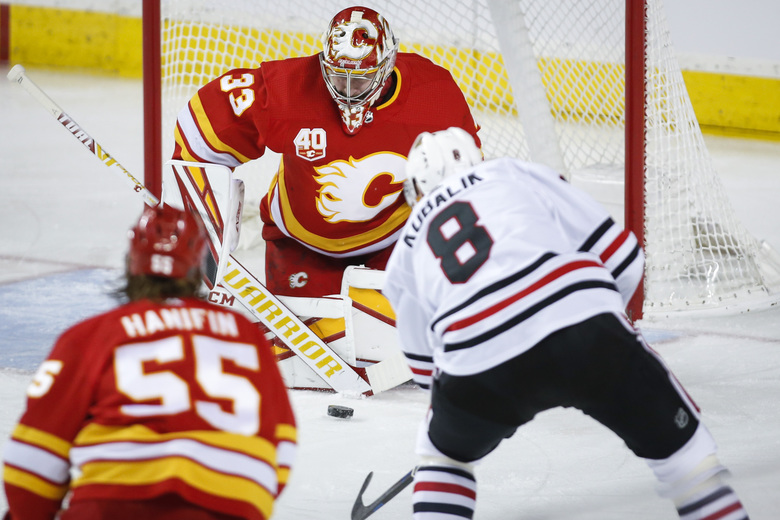 Chicago Blackhawks' Dominik Kubalik, right, has his shot blocked by Calgary Flames goalie David Rittich during the first period of an NHL hockey game Tuesday, Dec. 31, 2019, in Calgary, Alberta. (Jeff McIntosh/The Canadian Press via AP)