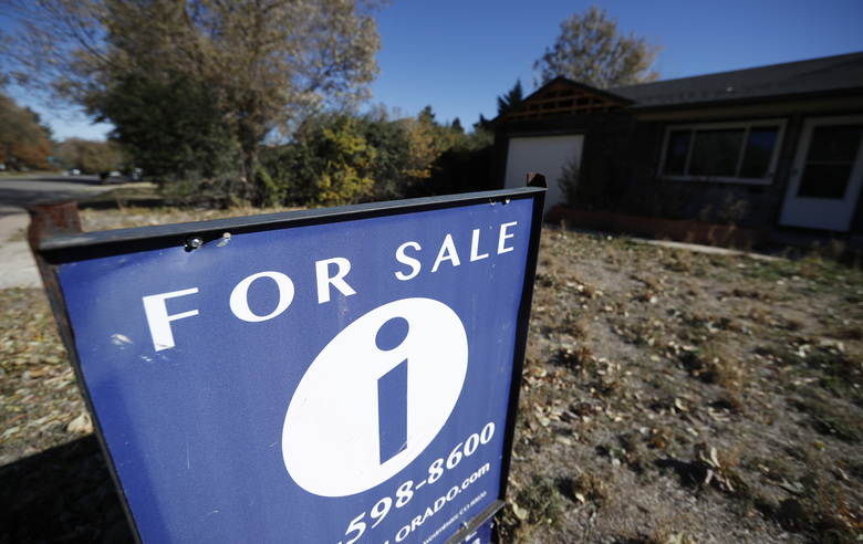 FILE – In this Oct. 22, 2019, file photo a sign stands outside a home for sale in southeast Denver. On Thursday, Dec. 5, Freddie Mac reports on this week's average U.S. mortgage rates. (AP Photo/David Zalubowski)
