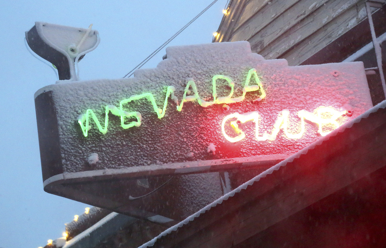 In tis Tuesday, Nov. 26, 2019, photo, the Nevada Club sign looks a little frosty in the evening as snow falls to as low as 1,500 feet in elevation in Grass Valley, Calif. Forecasters said a new storm is expected to bring California several feet of mountain snow, rain and gusty winds through the weekend.  (Elias Funez/The Union via AP)