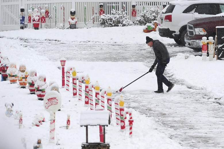 A man shovels snow amid Christmas decorations on Manor Drive in Kingston Township, Pa., Monday Dec. 2, 2019. A final wallop of a seemingly endless winter storm that impacted most of the country over the long holiday weekend is bearing down on the East, dumping heavy snow, shuttering schools and stymieing travel in the region Monday. (Mark Moran/The Citizens' Voice via AP)