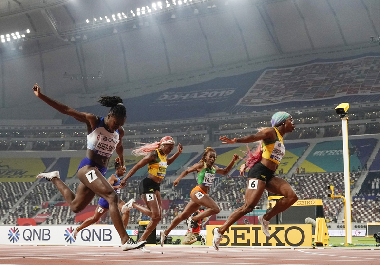 Shelly-Ann Fraser-Pryce (6), of Jamaica, finishes ahead of Dina Asher-Smith (7), of Britain, and Marie-Josée Ta Lou (4), of The Ivory Coast, in the women's 100-meter final at the World Athletics Championships in Doha, Qatar, Sept. 29, 2019. (AP Photo/David J. Phillip)