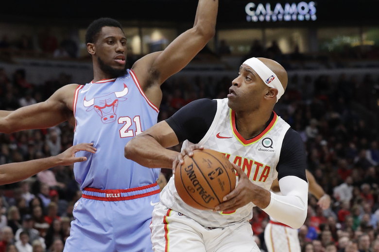 Atlanta Hawks guard/forward Vince Carter, right, looks to pass as Chicago Bulls forward Thaddeus Young guards during the first half of an NBA basketball game Saturday, Dec. 28, 2019, in Chicago. (AP Photo/Nam Y. Huh)