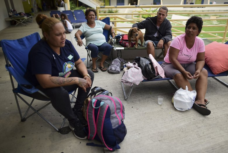 From left, Alma Torres Nazario, Olga Ramos, Danny Ramos and Elizabeth Ramos sit in an outdoor area of the Bernardino Cordero Bernard High School amid aftershocks and no electricity in Ponce, Puerto Rico, on  Wednesday, Jan. 8, 2020. More than 250,000 Puerto Ricans remained without water on Wednesday and another half a million without power, which also affected telecommunications. (Carlos Giusti / The Associated Press)
