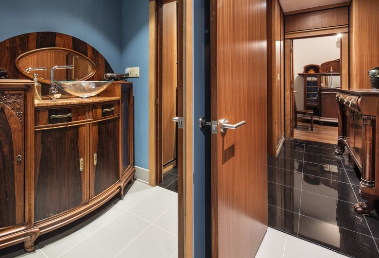 """The vanity in the powder room mixes styles and woods, says Roger Wallace. """"People try to put Art Nouveau and Art Deco in these categories, but the fact is, these were made by real people. [One] portion is wholly Art Nouveau with the carving, but you can tell it was done after Art Nouveau because it's very Art Deco with the streamlining. It's like, 'Yeah, but Uncle Phil still works for us and carves, and that's his thing. We can't just fire Uncle Phil, so we'll do both.' It might sound very clean and neat in the history books, but it's really not."""" (Steve Ringman / The Seattle Times)"""