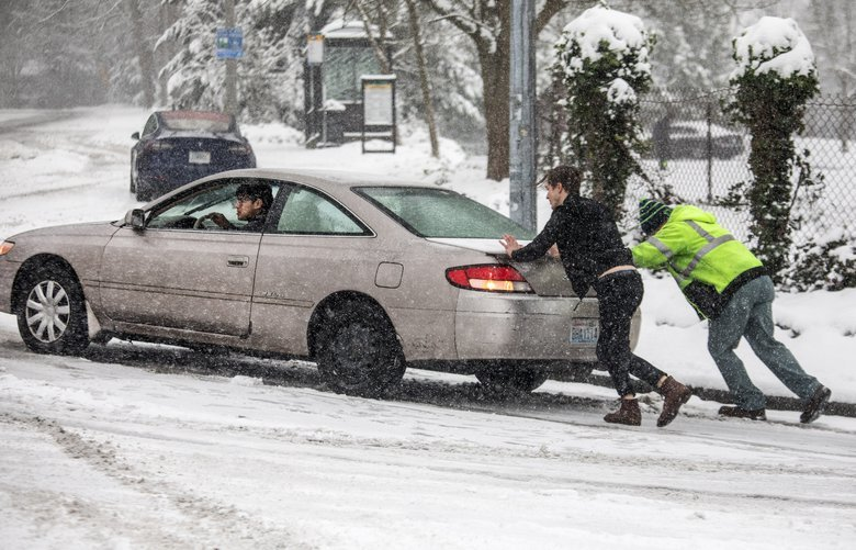 Monday, January 13, 2019.  Pedestrians in Kirkland try to push a car up NE 70th Place near in compact slippery snow. 212662