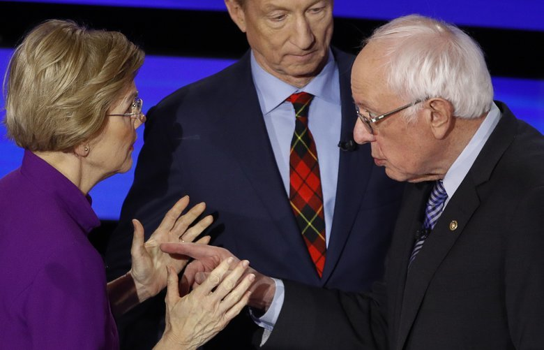 Democratic presidential candidate Sen. Elizabeth Warren, D-Mass., left and Sen. Bernie Sanders, I-Vt., talk Tuesday, Jan. 14, 2020, after a Democratic presidential primary debate hosted by CNN and the Des Moines Register in Des Moines, Iowa., as businessman Tom Steyer looks on. (AP Photo/Patrick Semansky) IAKJ178 IAKJ178
