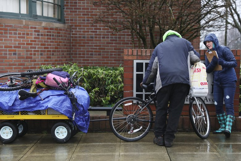 Volunteer Holly Shelton, right, is not able to get a survey from a man she encountered in Everett. The man, who will not be included in Snohomish County's homeless count because he didn't take the survey, was given a warm hat and socks. (Ken Lambert / The Seattle Times)