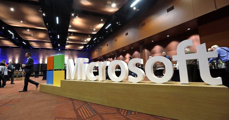 In this Nov. 30, 2016, file photo a man walks past a Microsoft sign at the annual Microsoft shareholders meeting in Bellevue, Wash.  (Elaine Thompson / AP)
