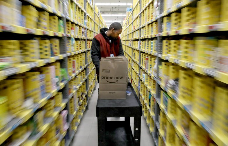 an Amazon employee quickly moves his cart through rows of shelving at the Amazon grocery site in SoDo.    Thursday March 21, 2019  209688 209688
