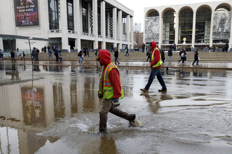 Workers walk through a flooded street in front of Lincoln Center for the Performing Arts, in New York, Monday, Jan. 13, 2020. A water main break flooded streets on Manhattan's Upper West Side near Lincoln Center and hampered subway service during the Monday morning rush hour. (AP Photo/Richard Drew)