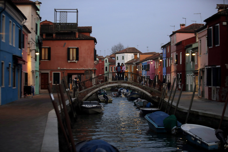 In this image taken on Thursday, Jan. 16, 2020, people stand on a bridge at the Burano island, Italy. The Venetian island of Burano's legacy as a fishing village remains the source of its charms: the small colorful fishermen's cottages, traditional butter cookies that were the fishermen's sustenance at sea and delicate lace still stitched by women in their homes. As the island's population dwindles, echoing that of Venice itself, so too are the numbers of skilled artisans and tradespeople who have kept the traditions and economy alive. (AP Photo/Luca Bruno)