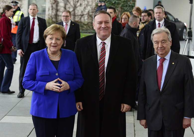 German Chancellor Angela Merkel, left, greets United Nations Secretary General Antonio Guterres, right, and U.S. Secretary of State Mike Pompeo, center, during arrivals for a conference on Libya at the chancellery in Berlin, Germany, Sunday, Jan. 19, 2020. German Chancellor Angela Merkel hosts the one-day conference of world powers on Sunday seeking to curb foreign military interference, solidify a cease-fire and help relaunch a political process to stop the chaos in the North African nation. (AP Photo/Jens Meyer)