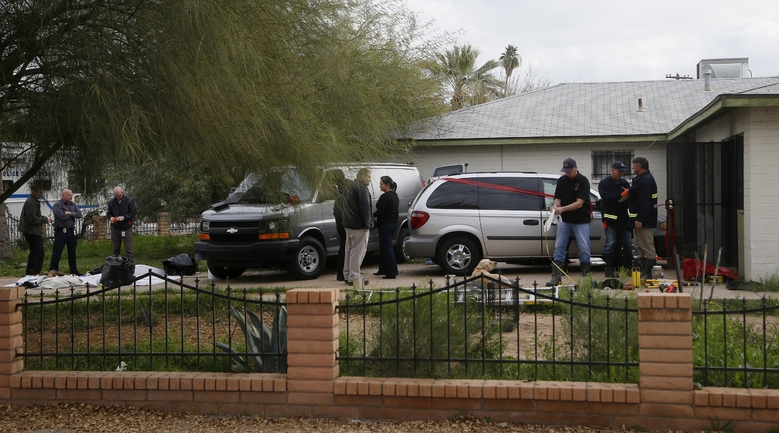Phoenix Police Department and Fire Department investigators work at a home where skeletal remains were found Wednesday, Jan. 29, 2020, in Phoenix. The remains have been found at a house where authorities previously removed at least one child as part of a child abuse investigation in which both parents of that child were in custody, police said Wednesday. (AP Photo/Ross D. Franklin)