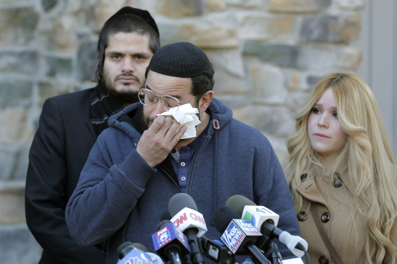 CORRECTS SPELLING OF JOSEF NEUMANN'S DAUGHTER'S LAST NAME TO KOHEN INSTEAD OF COHEN – Surrounded primarily by family, David Neumann, center, wipes his eyes as he speaks to reporters in New City, N.Y., Thursday, Jan. 2, 2020, about his father, Josef Neumann, who was critically injured in an attack on a Hanukkah celebration. Nicky Kohen, Josef Neumann's daughter, told reporters she hopes her father regains consciousness and finds a changed world while making an emotional plea to end hatred and anti-Semitism. Their 72-year-old father has been unconscious since he was wounded Saturday in a machete attack at a rabbi's home in Monsey, N.Y. (AP Photo/Seth Wenig)